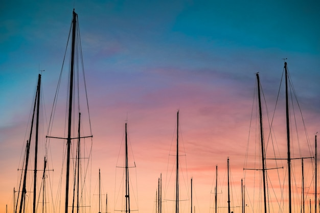 Beautiful shot of a silhouette of sailboat masts  at sunset Free Photo