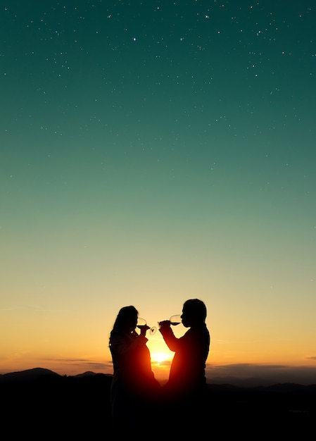 Beautiful shot of silhouettes of a couple drinking wine at sunset Free Photo