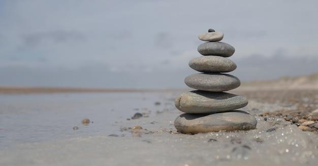 Bello colpo di una pila di rocce sulla spiaggia - concetto di stabilità di affari Foto Gratuite