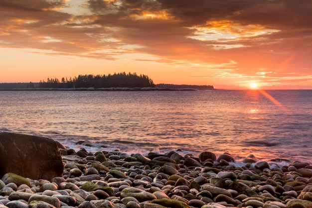 Beautiful shot of a stony  seashore  and the setting sun in the background Free Photo
