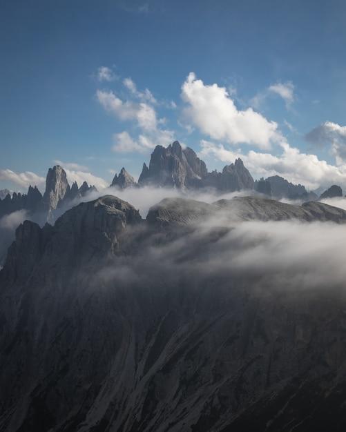 Bellissimo scatto del parco naturale tre cime parzialmente coperto di nuvole a dobbiaco, italia Foto Gratuite
