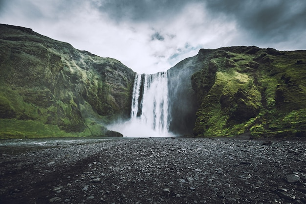 Beautiful shot of a waterfall coming down from mountains Free Photo