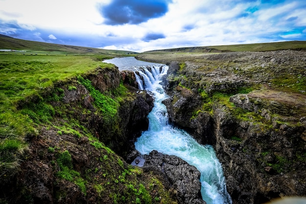Beautiful shot of waterfall flowing down in the middle of rocky hills under a cloudy sky Free Photo