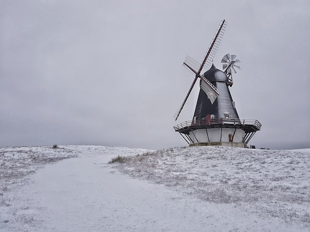 Beautiful shot of a windmill in the middle of a winter field Free Photo
