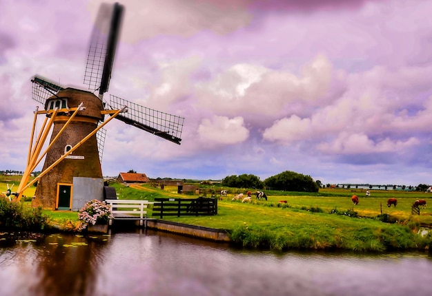 Beautiful shot of a windmill near the lake under a cloudy sky in holland Free Photo