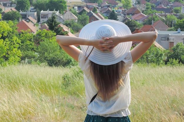 Bellissimo scatto di una donna che indossa un cappello bianco godendosi la vista e l'aria fresca in un campo di erba Foto Gratuite