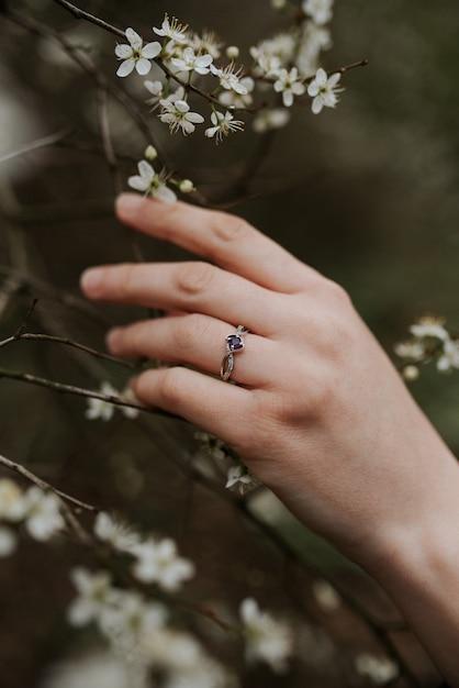 柔らかい女性の手に紫色のダイヤモンドが付いた美しいシルバーリング 無料写真