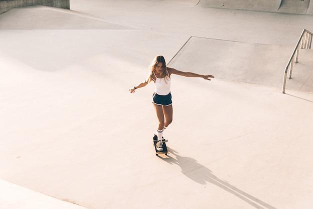 スケートパークで美しいスケーターガールライフスタイルの瞬間 Premium写真