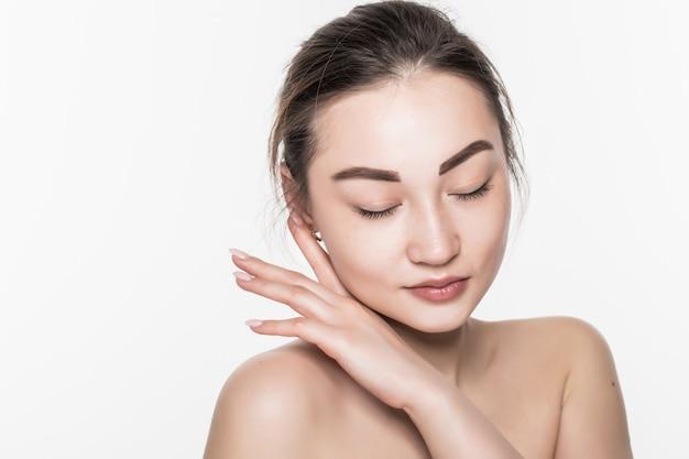 Женщина красивой заботы кожи азиатская наслаждается и ослабляет изолирована на белой стене. Бесплатные Фотографии
