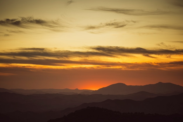 Beautiful sky on yellow shades with mountains Free Photo