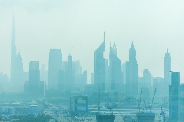 낮 빛에 모래 먼지로 둘러싸인 두바이의 아름다운 스카이 라인 무료 사진
