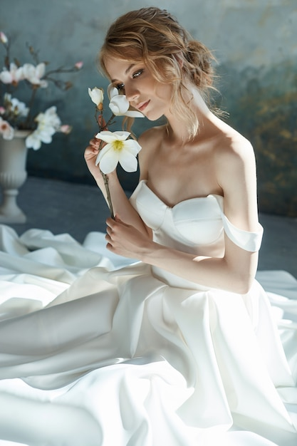 Beautiful slender blonde girl sitting on the floor in long white dress. Premium Photo
