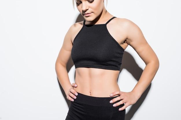 Bello modello femminile snello in vestiti di montaggio neri che posano sopra bianco Foto Gratuite