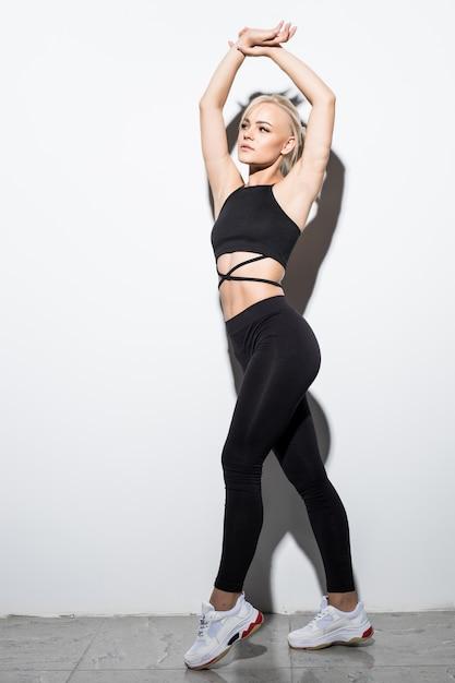Bella ragazza snella in vestiti di montaggio neri che posano sopra il bianco Foto Gratuite