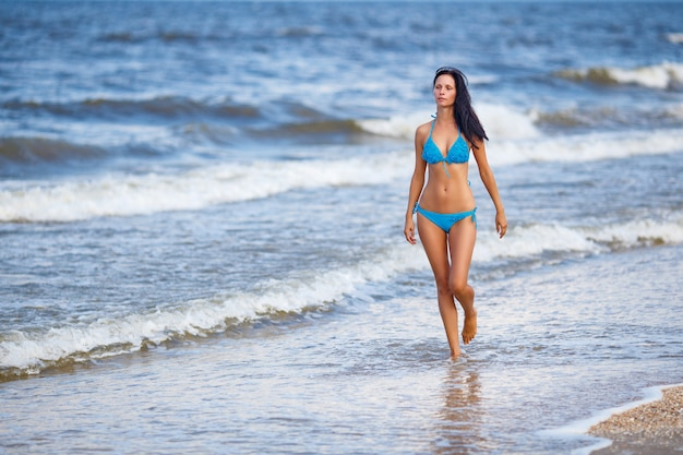 Beautiful slender woman in a blue swimsuit walking on the beach Premium Photo