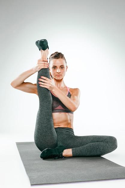 Bella bruna sottile facendo alcuni esercizi di stretching in palestra Foto Gratuite