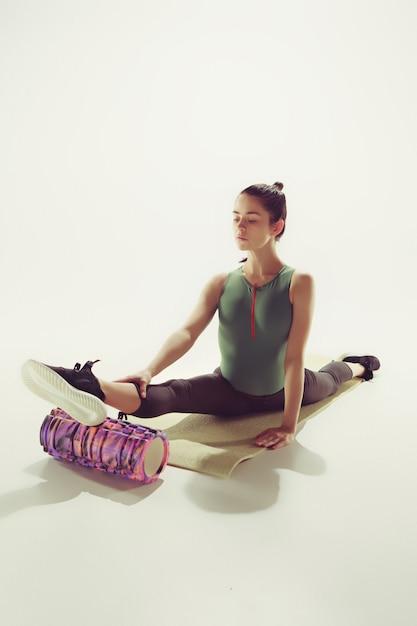 ジムでいくつかのストレッチ体操をしている美しいスリムなブルネット 無料写真