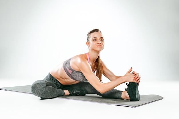 ジムでストレッチ体操をしている美しいスリムなブルネット 無料写真