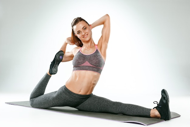 체육관에서 몇 가지 스트레칭 운동을 하 고 아름 다운 슬림 갈색 머리 무료 사진
