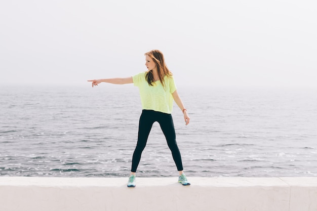 Beautiful slim girl in green sportswear shows the direction of the hand on the background of the sea Premium Photo