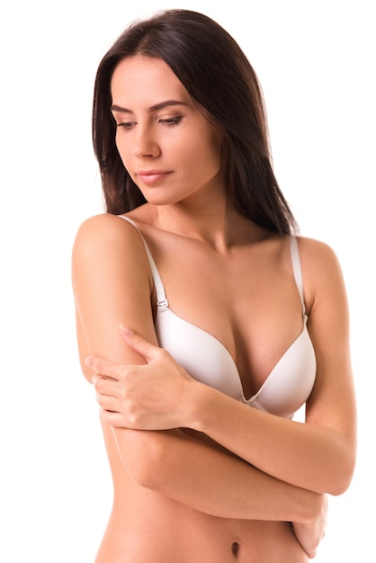 Beautiful slim girl in white lingerie is posing at camera. Premium Photo