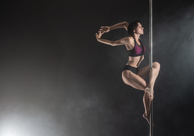 Beautiful slim girl with pylon. female pole dancer dancing on black Premium Photo