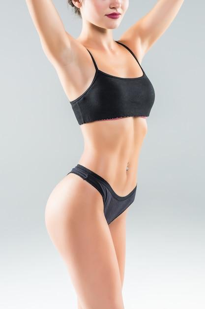 Красивое стройное женское тело с загаром на белой стене Бесплатные Фотографии