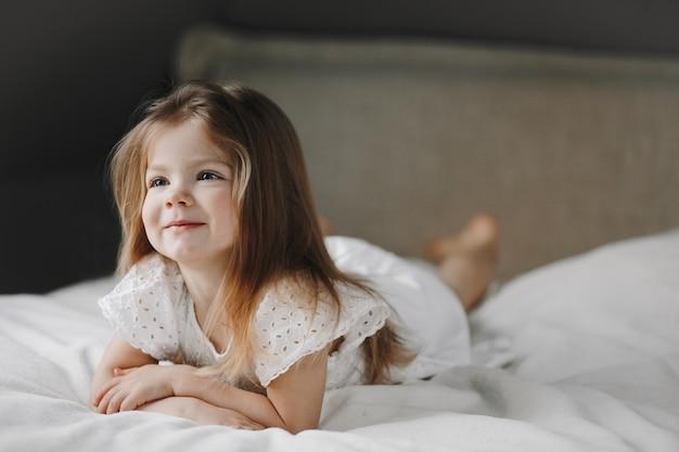 Красивая маленькая кавказская девушка лежит на белой кровати, одетая в белое платье и улыбается, и смотрит в сторону Бесплатные Фотографии