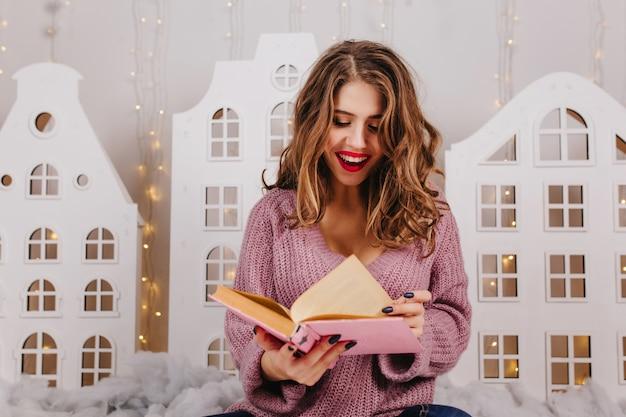 아늑한 크리스마스 분위기에서 재미있는 책을 읽고 밝은 립스틱으로 아름 다운 스마트 갈색 머리. 곱슬 머리를 가진 여자의 초상화 무료 사진