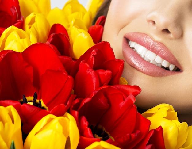 Un bel sorriso di denti sani della giovane donna. metà volto di una donna abbastanza felice con i tulipani Foto Gratuite