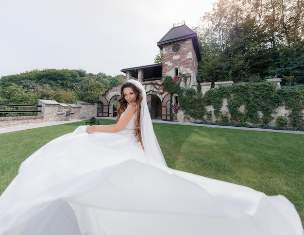 Beautiful smiled bride in luxury dress on the grass backyard of the old building, Free Photo