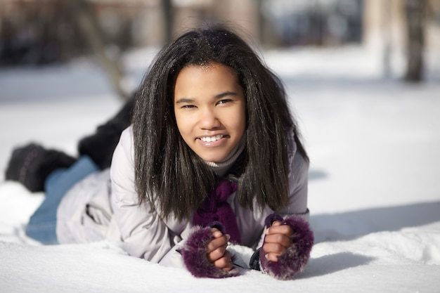 Beautiful smiling american black female lying in the snow outdoors Free Photo