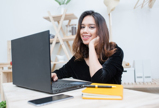 Beautiful smiling asian student woman learning from online education service, young asian woman doing homework with computer laptop , notebook and smart phone Premium Photo
