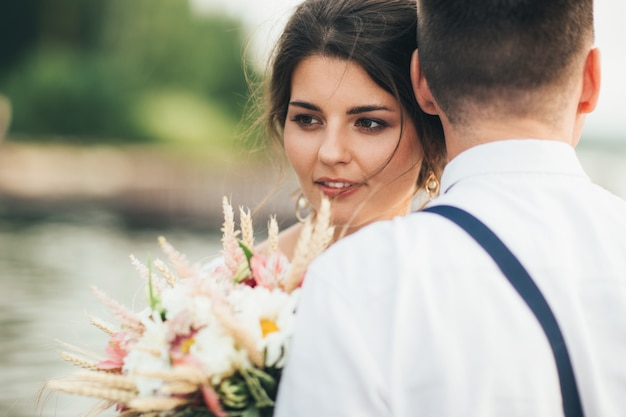 Beautiful smiling bride brunette young woman with boho style bouquet with groom Premium Photo