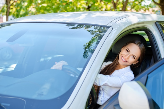 Beautiful smiling brunette girl behind the wheel of a car Premium Photo
