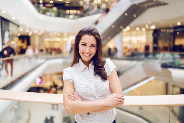 Beautiful smiling caucasian brunette in shirt standing in shopping mall with arms crossed. Premium Photo
