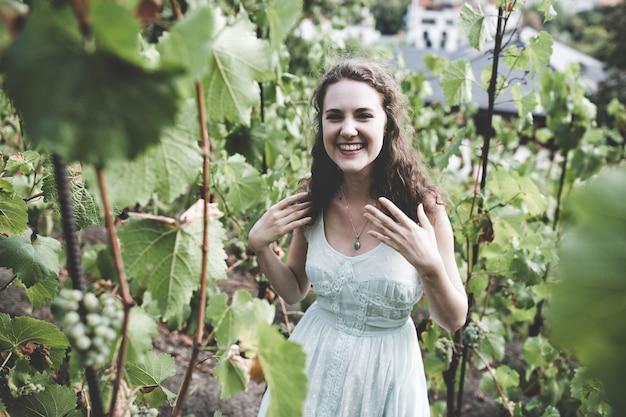 Красивая улыбающаяся брюнетка вьющимися волосами в голубом простом платье на винограднике Premium Фотографии