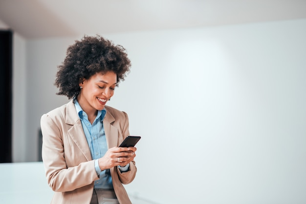 Beautiful smiling curly-haired businesswoman using smarphone indoors, copy space. Premium Photo