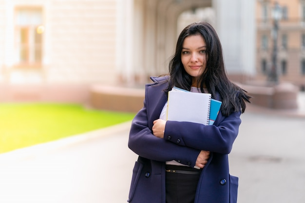 Beautiful smiling girl brunette student holding notebooks and textbooks, stands at university Premium Photo