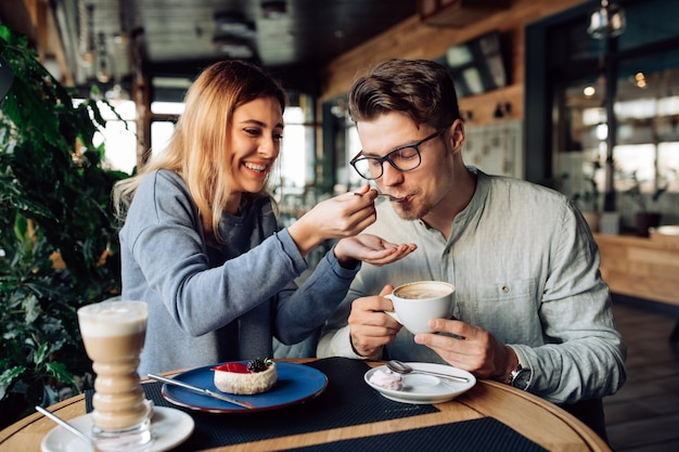 Beautiful smiling girl feeds her handsome boyfriend, eating tasty cake and drinking coffee Free Photo