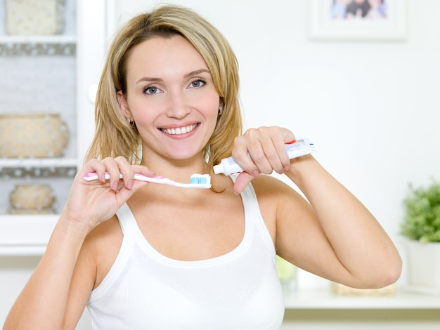 美しい笑顔の女の子は、歯磨き粉で歯ブラシを保持します 無料写真