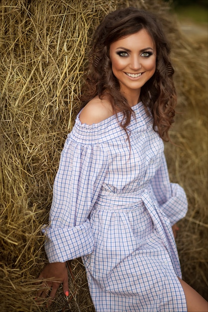 Beautiful smiling girl near a hay bale in the countryside Premium Photo