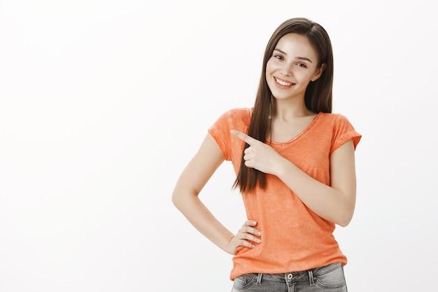 아름 다운 미소 매력적인 소녀, 손가락 왼쪽 상단을 가리키는, 배너 및 프로모션 시연 무료 사진