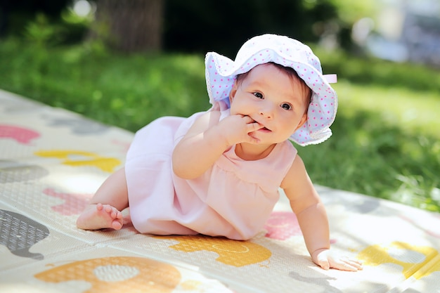 Beautiful smiling kid playing in the garden. happy cute  infant having fun in the park. sweet sunny baby in the panama hat Premium Photo