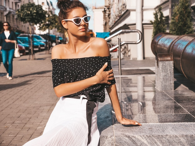 Beautiful smiling model dressed in elegant summer clothes.sexy carefree girl sitting in the street.trendy modern businesswoman in sunglasses having fun Free Photo