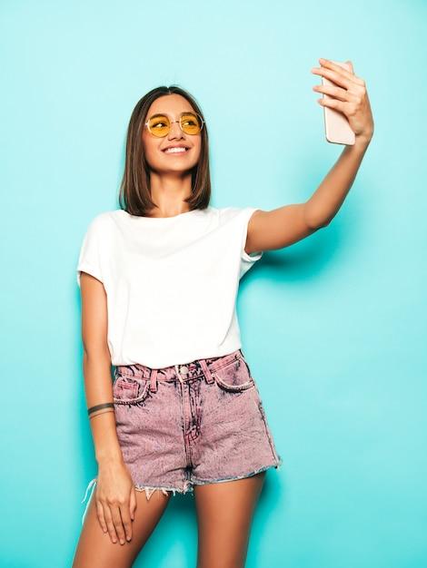 Красивая улыбающаяся модель в летней хипстерской одежде. сексуальная беззаботная девушка позирует в студии возле синей стены в джинсах шорты. модная и забавная женщина, делающая фотографии автопортрета селфи на смартфоне Бесплатные Фотографии