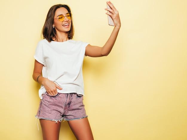 Красивая улыбающаяся модель в летней хипстерской одежде. сексуальная беззаботная девушка позирует в студии возле желтой стены в джинсах шорты. модная и забавная женщина, делающая фотографии автопортрета селфи на смартфоне Бесплатные Фотографии