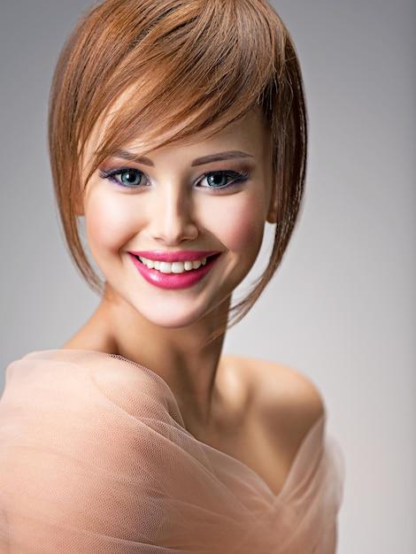 スタイルの髪型を持つ美しい笑顔の赤毛の女の子。大きな青い目をしたセクシーな若い女性の肖像画。ファッションモデルのポーズ 無料写真