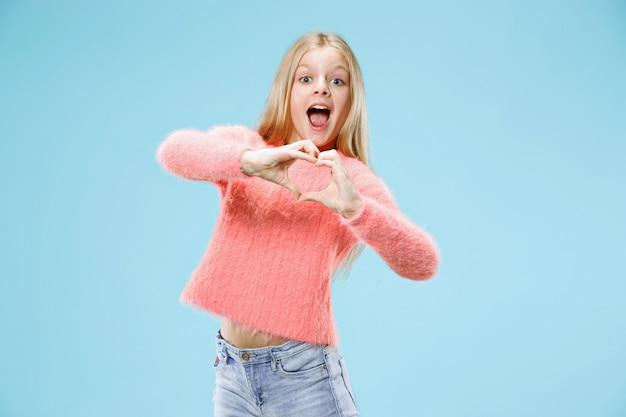 Красивая улыбающаяся девочка-подросток делает форму сердца руками на синем. Бесплатные Фотографии