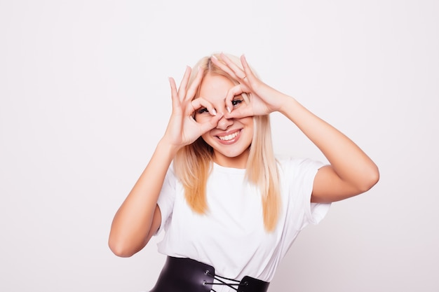 Красивая улыбающаяся девочка-подросток показывает очки из пальцев, Бесплатные Фотографии